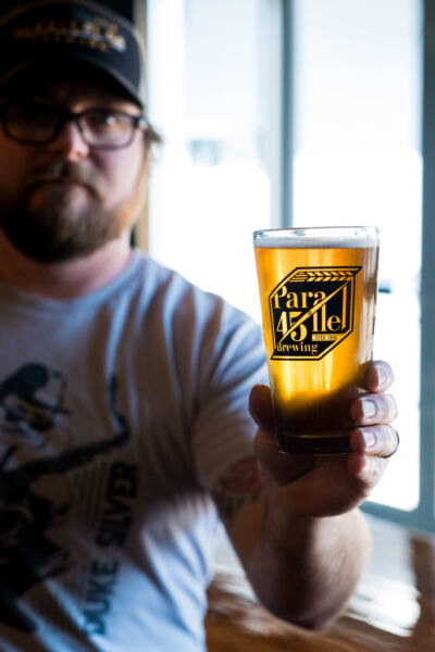 Parallel 45 Brewing co-owner Ryan Booth holding beer in custom glass