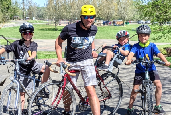 A dad and his kids ready to ride bikes