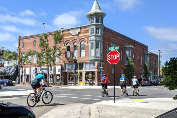 Bike Indy Oregon cyclers turning onto Main St in Independence