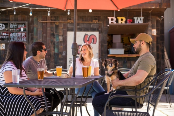 Four friends sit on the BREW Patio