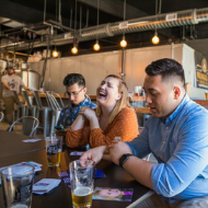Parallel 45 Brewing group playing cards and laughing over beer inside
