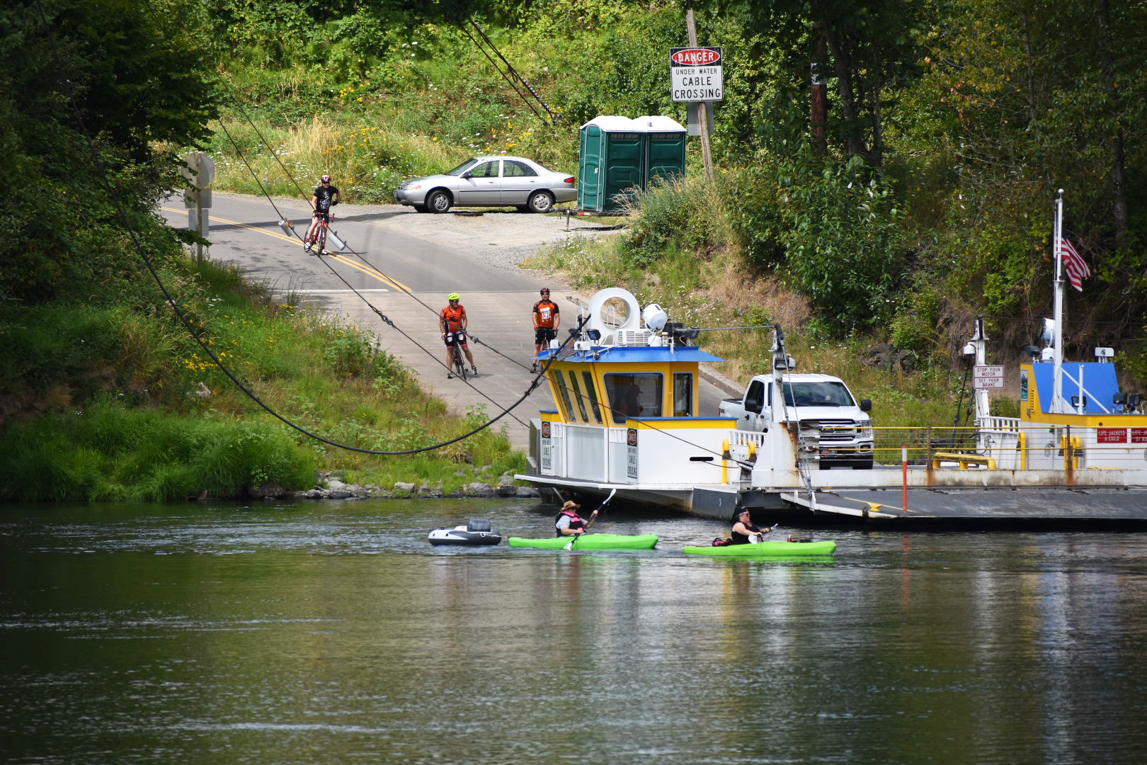 A river ferry with bicyclists waiting and kayaks on the water