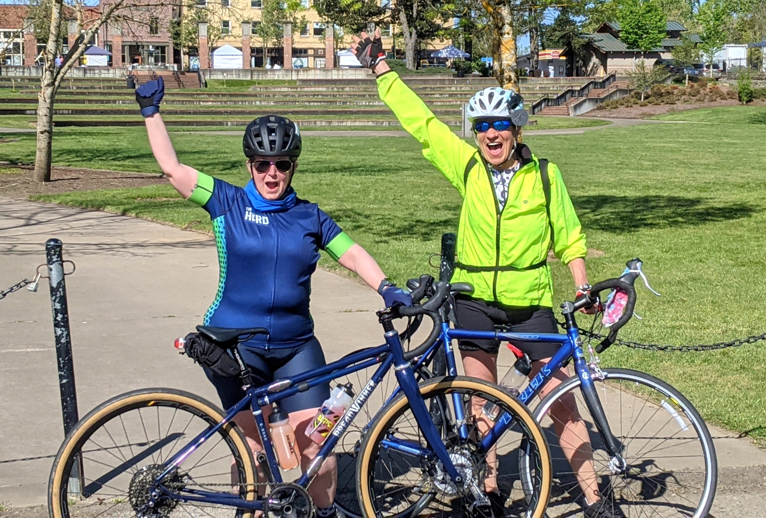 Two ladies with bikes celebrate finishing their ride