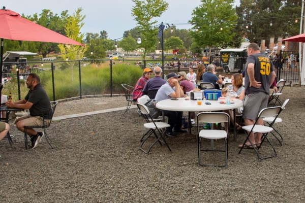 The back patio with several tables of people overlooking the amphitheater