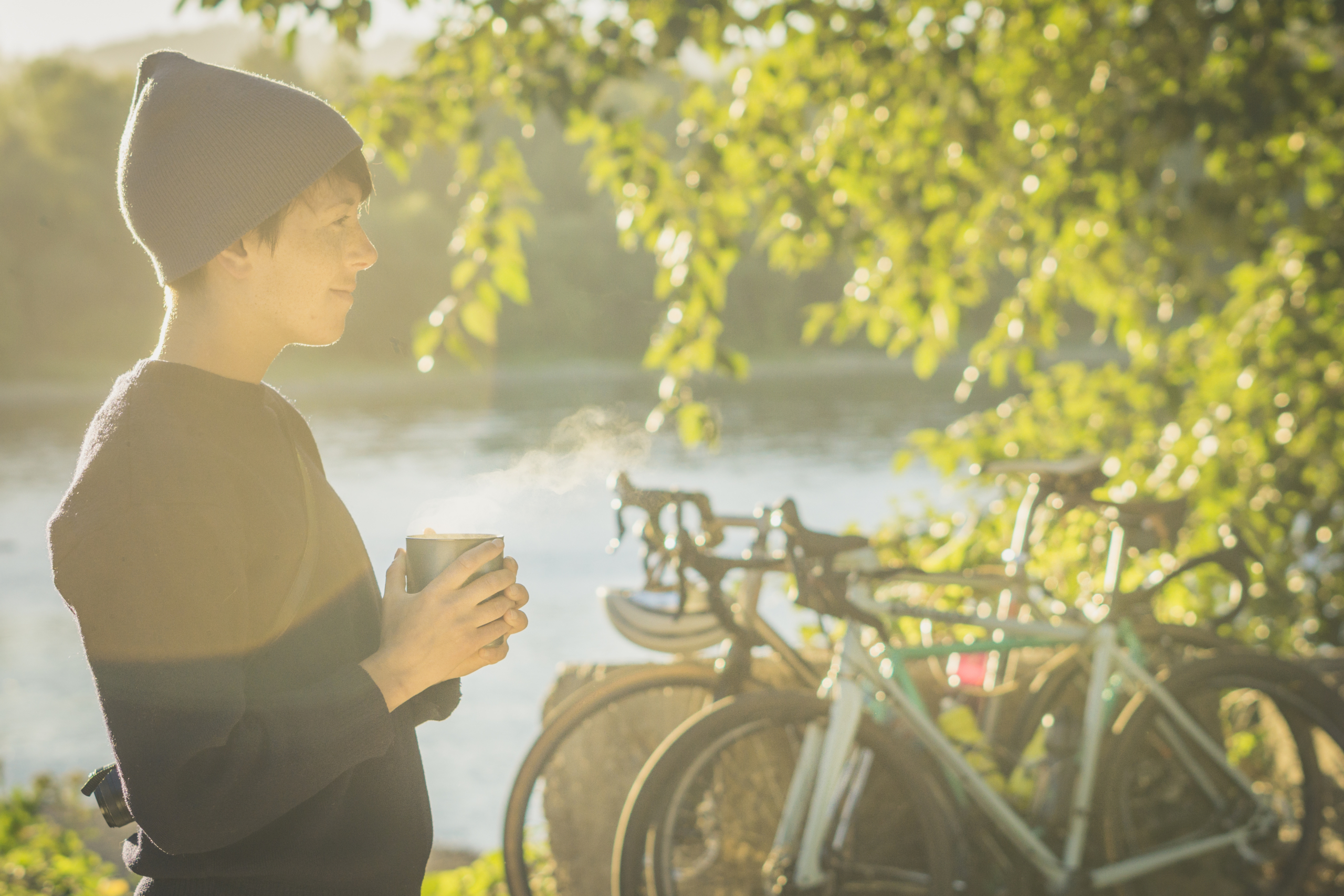Woman in the morning sun with bikes and river in the background